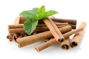 Cinnamon sticks on white reflective background.