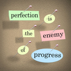 Perfection is the Enemy of Progress quote or saying with words on pieces of paper pinned to a bulletin board to illustrate you should not wait to take action until things are perfect